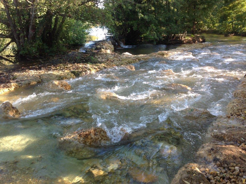 barrage sur un cours d'eau équipé d'une rampe en pente douce avec des blocs de pierre permettant la remontée des poissons