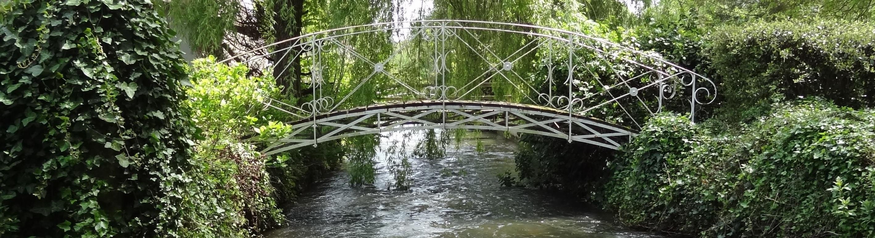 rivière claire qui passe souqs un pont en fer forgé